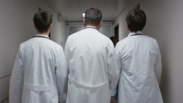 ds tre medici a piedi lungo corridoio di ospedale - camice da laboratorio video stock e b–roll