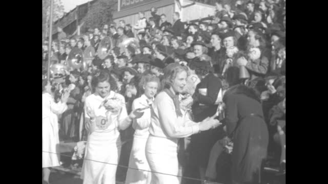three duck mascots on steamer trunk surrounded by clapping university of oregon cheerleaders / cheerleaders walk toward crowded stands clapping /... - ゴールポスト点の映像素材/bロール