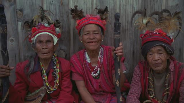 Three elderly Filipino women pose for a portrait.