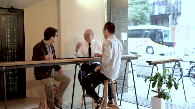 vidéos et rushes de three elderly men talking about work in a cafe - petit groupe de personnes