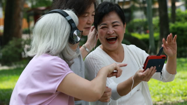 three elderly taiwanese friends laughing listening to music - headphones stock videos & royalty-free footage