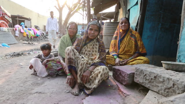 of three elderly women and a young child are sitting on the ground in front of a shanty in a small village at sunset on march 28, 2013 in bijapur,... - indian ethnicity stock-videos und b-roll-filmmaterial