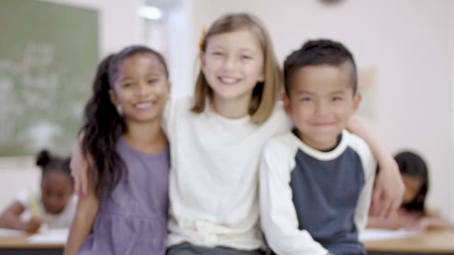 three elementary aged children smiling at camera - fatcamera stock videos and b-roll footage