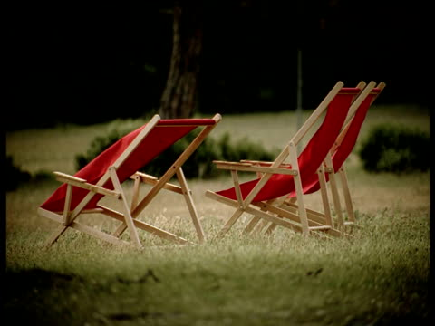 three empty red deck chairs on grass in park - outdoor chair stock videos & royalty-free footage