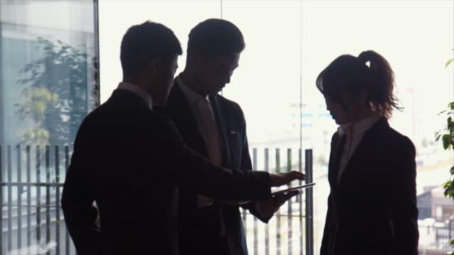 オフィス (スローモーション) で 3 つの起業家ブリーフィング - 説明する点の映像素材/bロール