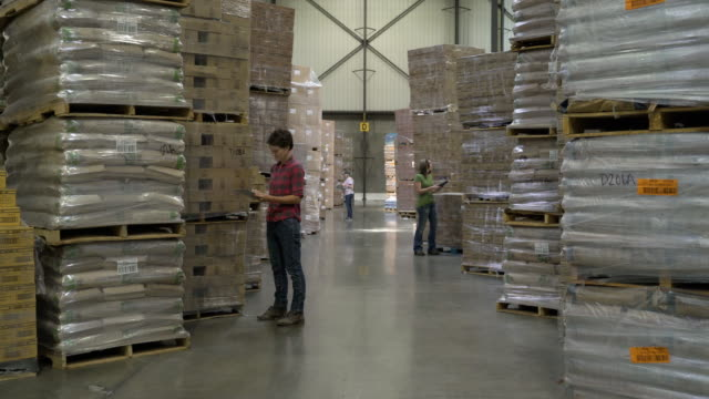 Three female colleagues standing by stock on pallets, holding and writing on clipboards