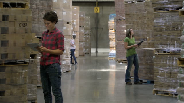 Three female colleagues standing by stock on pallets, writing on clipboards