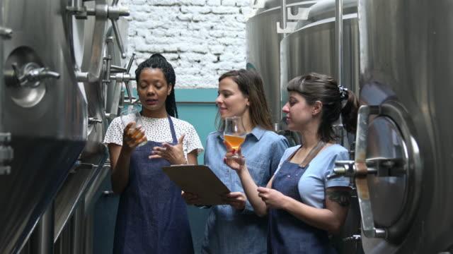 tre kvinnliga hantverk bryggerierna ritning öl prov och kontroll kvalitet - dom bildbanksvideor och videomaterial från bakom kulisserna