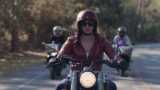 SLO MO. Three female friends drive down secluded wooded highway on motorcycles.
