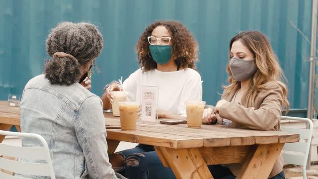 vidéos et rushes de trois amies se rencontrent pour un café au café extérieur - table de pique nique
