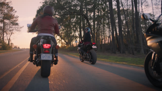 slo mo. three female friends on motorcycles laugh together on sunset drive. - motorrad stock-videos und b-roll-filmmaterial