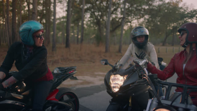 SLO MO. Three female friends on motorcycles stop for a chat on secluded forest road.
