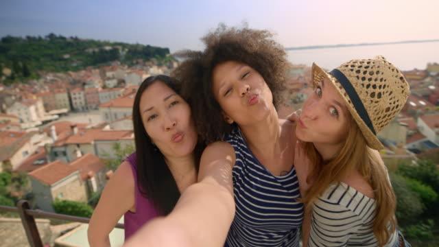 stockvideo's en b-roll-footage met drie vriendinnen nemen van selfies op een loopbrug boven een kustplaatsje op een zonnige dag - zelfportret fotograferen