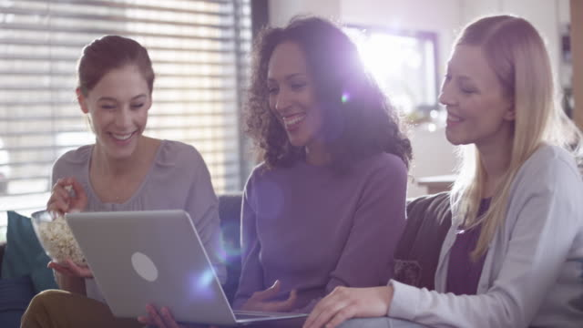 three female friends talking while using a laptop - only young women stock videos & royalty-free footage