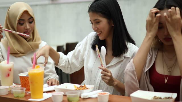 vídeos de stock, filmes e b-roll de três amigas degustação exótica cozinha asiática - sedento
