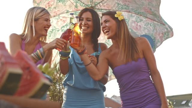 three female friends toasting with drinks at rooftop party - juice drink stock videos & royalty-free footage
