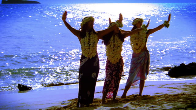 BLUE three female hula dancers in leis doing arm movements in unison / ocean in background / Hawaii