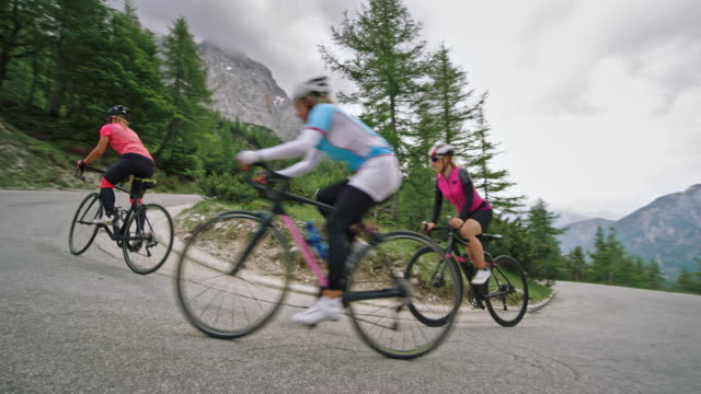 three female road cyclists riding up the road high in the mountains on a cloudy day - 40 44 years stock videos & royalty-free footage