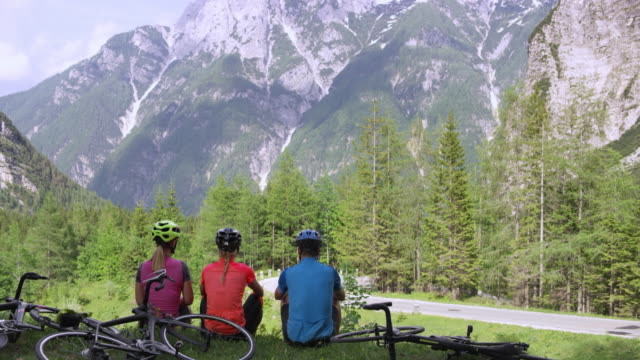 cs three female road cyclists taking a break and enjoying the beautiful view of the surrounding mountains - mountain pass stock videos & royalty-free footage