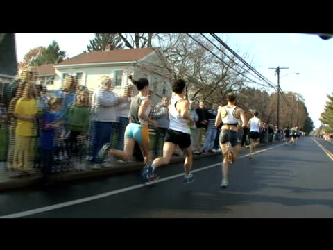vídeos y material grabado en eventos de stock de three female runners racing past spectators during the manchester road race three female runners race past spectators on january 01 2012 in... - salmini