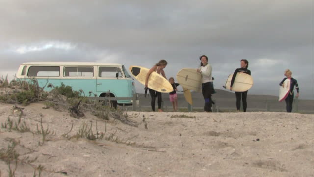 WS, Three female surfers with girl (6-7) and boy (12-13) carrying surfboards on beach, Cape Town, Western cape, South Africa