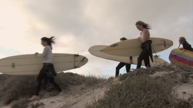 WS, PAN, Three female surfers with girl (6-7) and boy (12-13) carrying surfboards on san dune, Cape Town, Western cape, South Africa