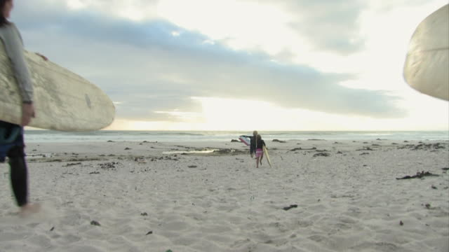 WS, Three female surfers with girl (6-7) and boy (12-13) carrying surfboards to ocean, rear view, Cape Town, Western cape, South Africa