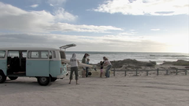 WS, Three female surfers with girl (6-7) and boy (12-13) removing surfboards from VW bus on beach, Cape Town, Western cape, South Africa