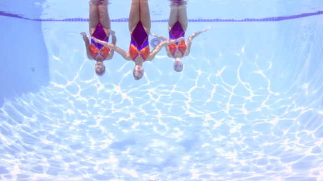 MS Three female synchronized swimmers treading water upside down while performing routine underwater view