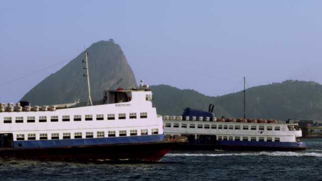 vídeos de stock e filmes b-roll de three ferry boats pass in front of sugar loaf mountain - 50 segundos ou mais