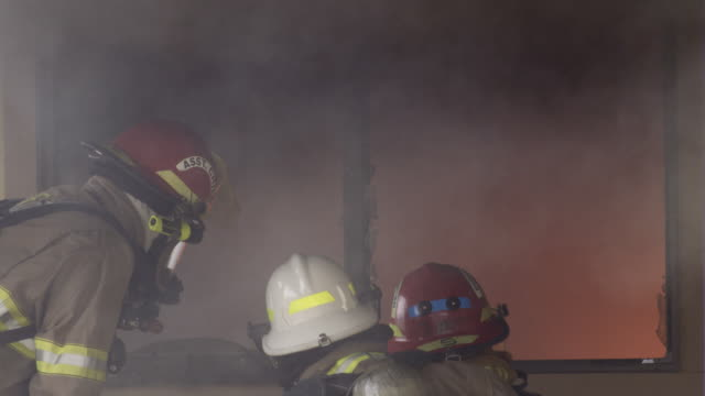 three firefighters in front of a glowing window spray a stream of water into the room - myrtle creek stock videos and b-roll footage