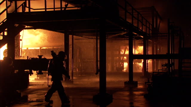 vidéos et rushes de three firemen walk through a fire training facility. - brasier