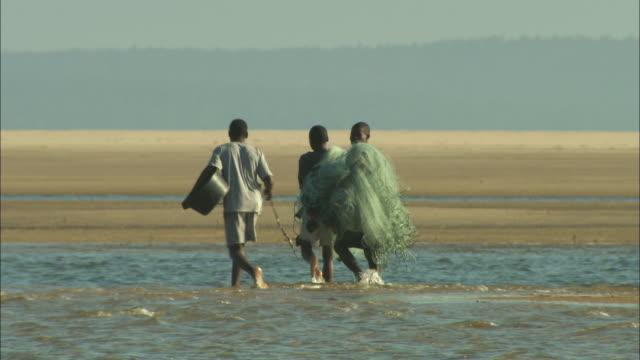 Three fishermen wade through water on the Zambezi River Delta.