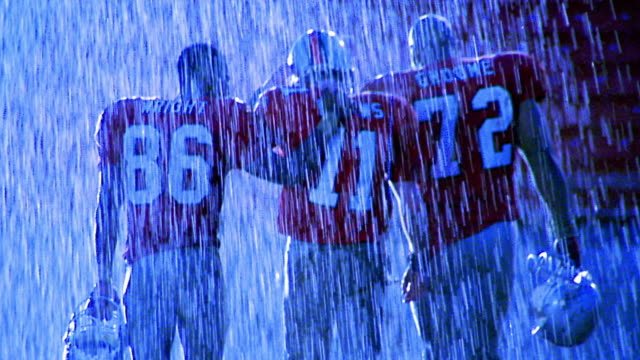 blue overexposed three football players walking away from camera in rain - only men stock videos & royalty-free footage