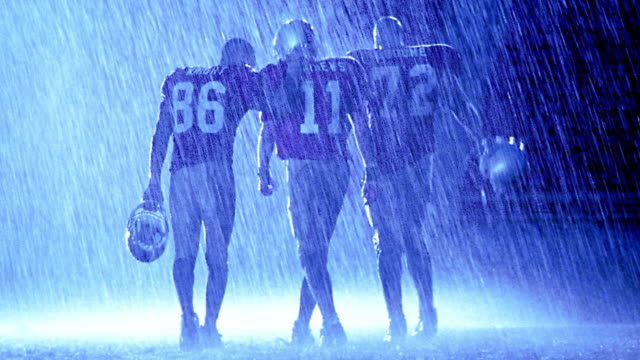 blue overexposed three football players walking away from camera in rain - overexposed stock videos & royalty-free footage