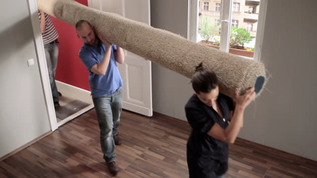 WS ZO Three friends carrying rolled up carpet into house / Berlin, Germany