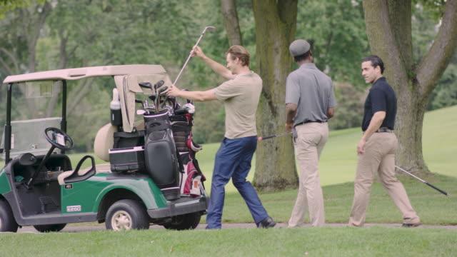 vidéos et rushes de trois amis de golf et de parler - terrain de golf