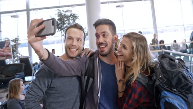 Three friends having a video call from the airport as they wait for their boarding