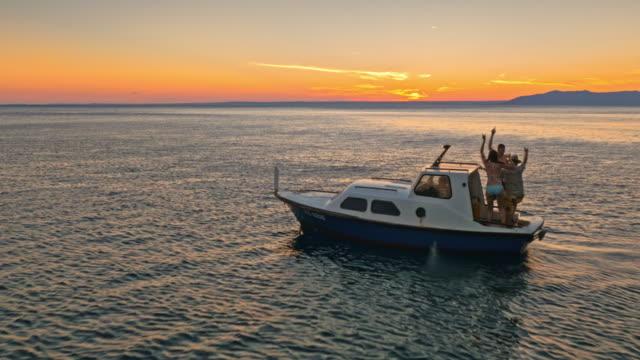 antenna tre amici che si divertono su una barca al crepuscolo - nautical vessel video stock e b–roll