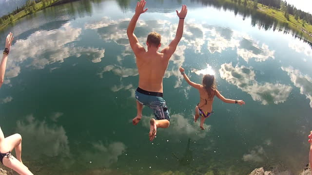 POV of three friends jumping into mtn lake