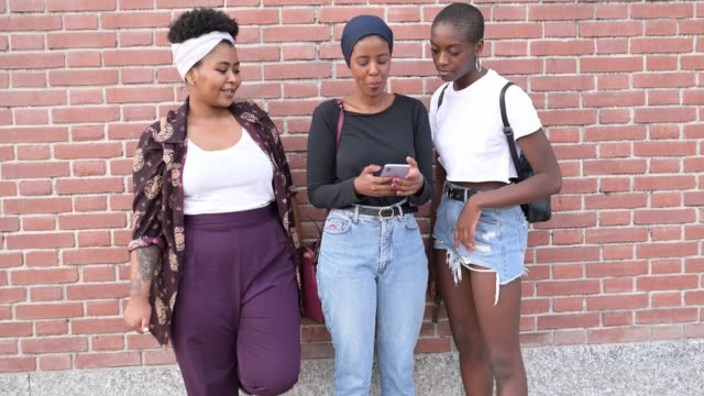 tre vänner tittar på en mobiltelefon bredvid en tegelvägg - milano bildbanksvideor och videomaterial från bakom kulisserna