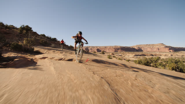 Three friends mountain bike over rocky terrain in Moab.