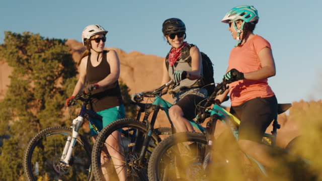 Three friends on mountain bikes talk and laugh on Moab desert trail.