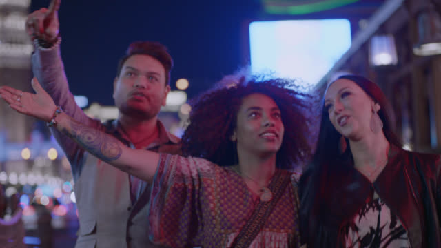 vidéos et rushes de three friends on night out walk down busy las vegas strip with arms locked. - découverte
