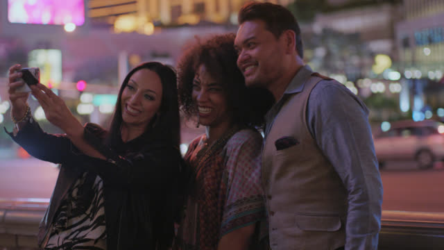 vídeos de stock, filmes e b-roll de three friends pose for selfies with smartphone on las vegas strip at night. - celular com câmera