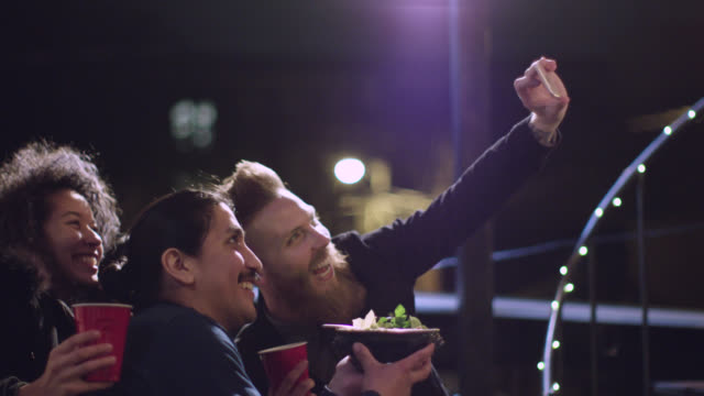 ms. three friends pose for smartphone selfie at rooftop party. - capturing an image stock videos and b-roll footage
