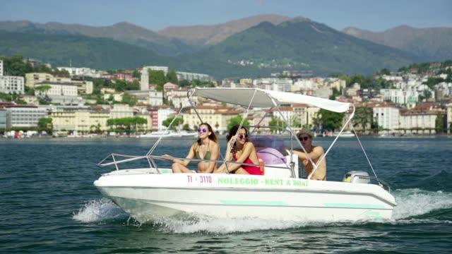 stockvideo's en b-roll-footage met drie vrienden motorboot in zwemkleding rijden op bergmeer met stad achter - eendelig zwempak