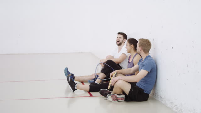 Three friends sitting on floor of racquetball court