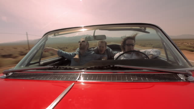 three friends smile, high-five, and hug as they ride in a convertible in the nevada desert. - collector's car stock videos and b-roll footage