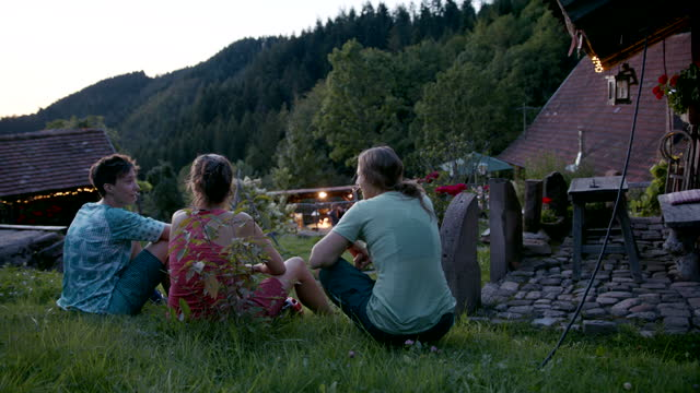 three friends taking a break outside of a mountain hut at sundown - mid adult stock videos & royalty-free footage
